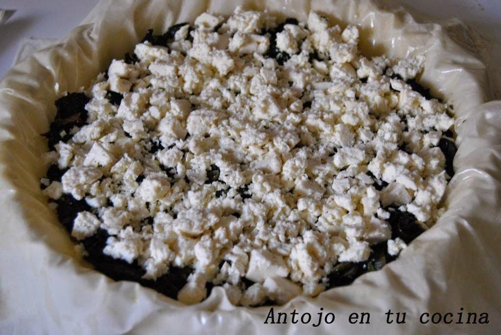Vertemos la mitad de las espinacas en nuestro molde cubierto por la masa filo, esparcimos el queso feta desmenuzado y cubrimos con el resto de espinacas.