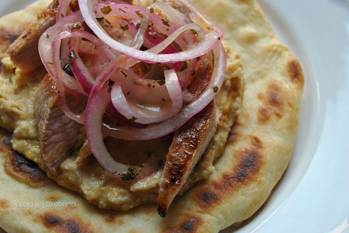 Pan naan con hummus, secreto iberico y cebolla macerada